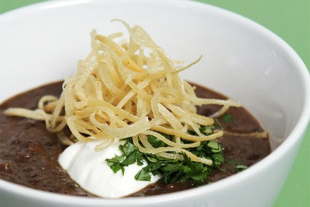 Black bean soup with pan-roasted poblano peppers and crispy shoestring tortillas