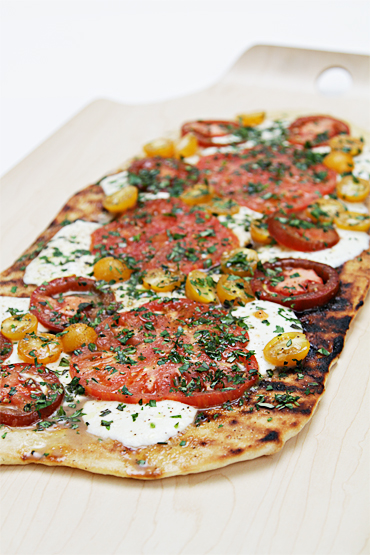 Grilled pizza with heirloom tomatoes and fresh herbs-lemon oil