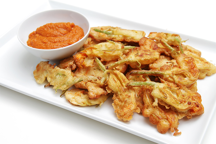 Beer-battered zucchini flower fritters with curried tomato coulis