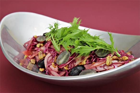 Shaved red cabbage and apple salad with black grapes and warm Cabernet vinaigrette