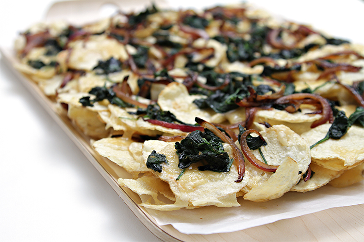 Potato nachos with smoked raclette, wilted spinach and caramelized red onion