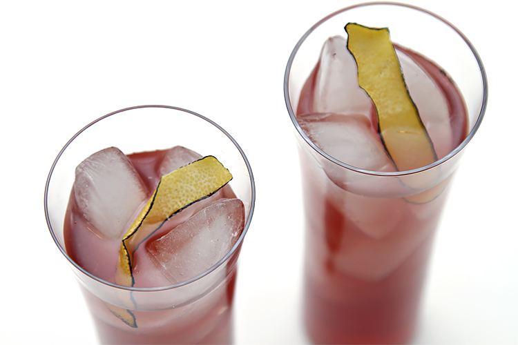 Blackcurrant cocktail with coconut water and burnt lemon peel